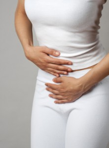 Woman-in-white-holding-stomach